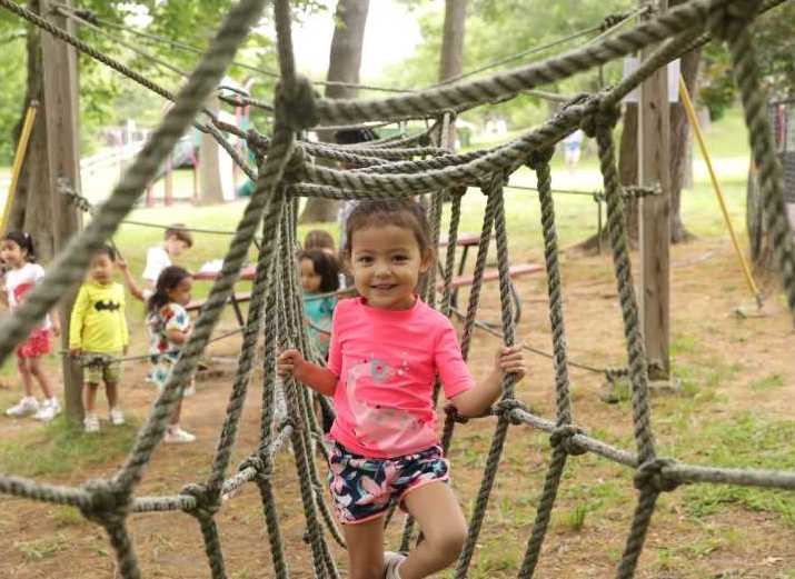 Preschool Camper Climbing through the ropes course.