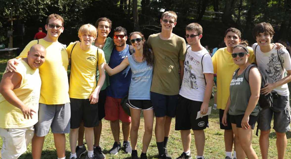 Campers on the Autism Spectrum With their Counselors Posing for A group SHot Smiling