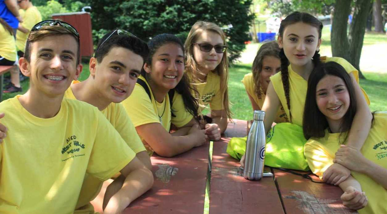 West Hills Leader in Training Campers Posing at a Picnic Table With Yellow Shirts