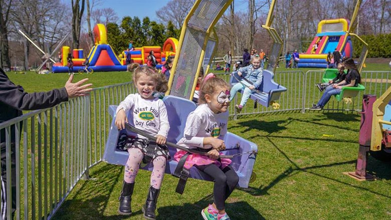Campers with Facepaint and West Hills shirts Riding a Carnival Ride at the Spring Carnival